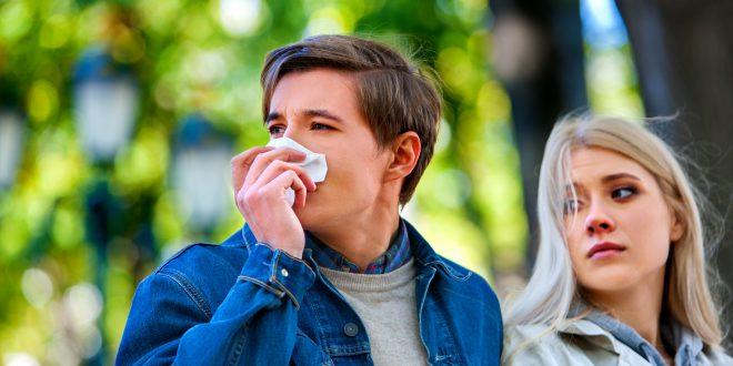 Spring allergies - blowing nose in handkerchief outdoor
